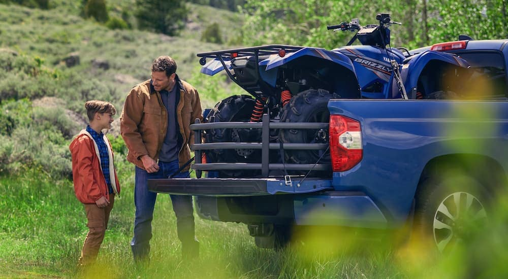 A father and son are next to a blue 2020 Toyota Tundra with a four-wheeler in the bed.