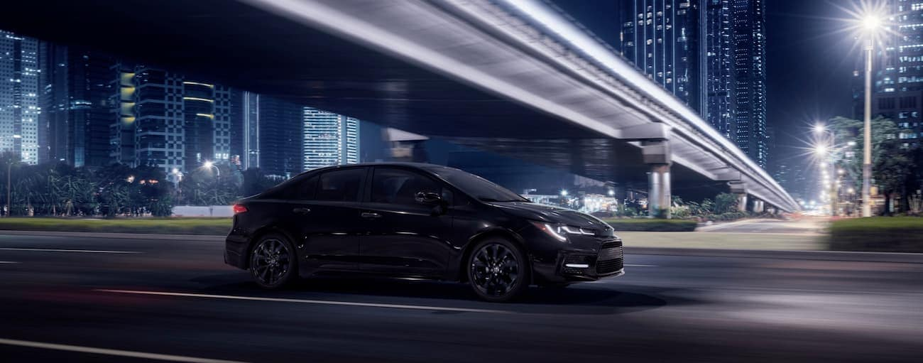 A black 2020 Toyota Corolla is drivign on a city highway at night.