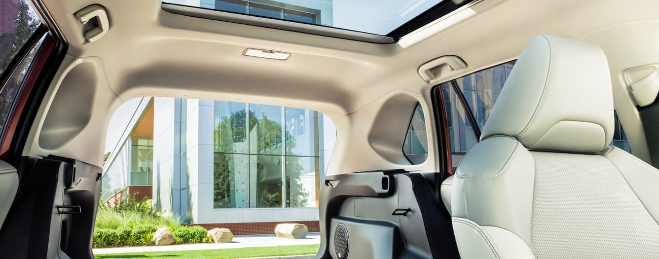 The white interior of a 2020 Toyota RAV4 Hybrid with a sun roof is shown.