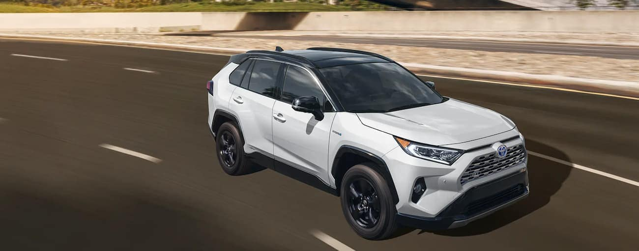 A white 2020 Toyota RAV4 Hybrid is driving on a highway near Indiana, PA.