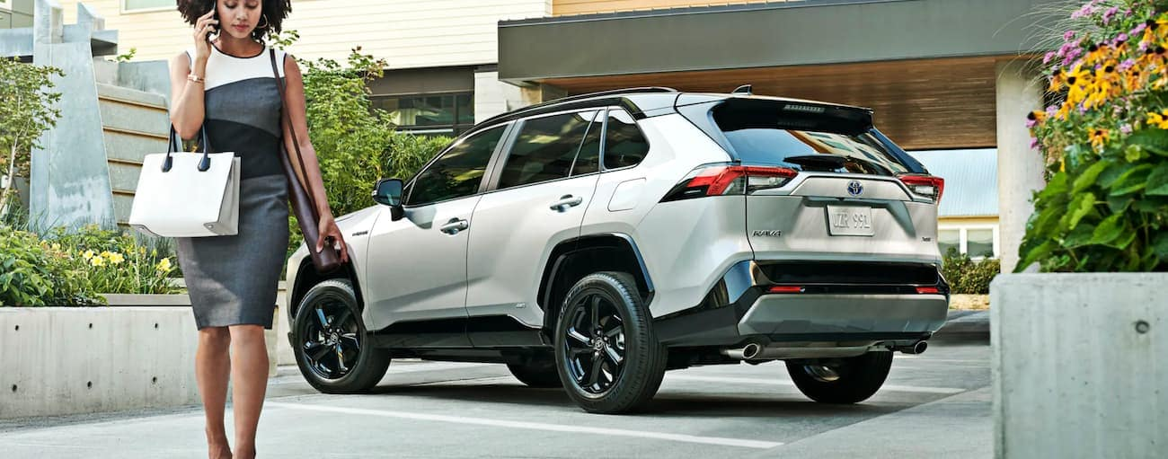 A woman is walking away from her white and black 2020 Toyota RAV4 Hybrid parked in front of a building.