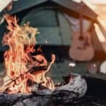 A campfire is in front of a tent and a guitar.