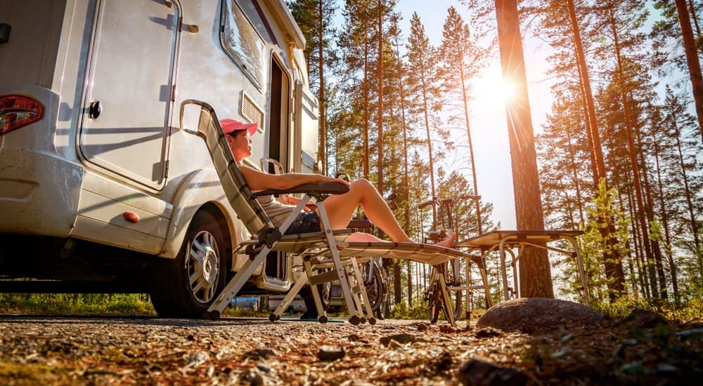 A woman is sitting in a chair outside of her RV at a campground in Pittsburgh, PA.