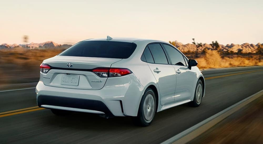 A white 2020 Toyota Corolla Hybrid is driving on a desert road.