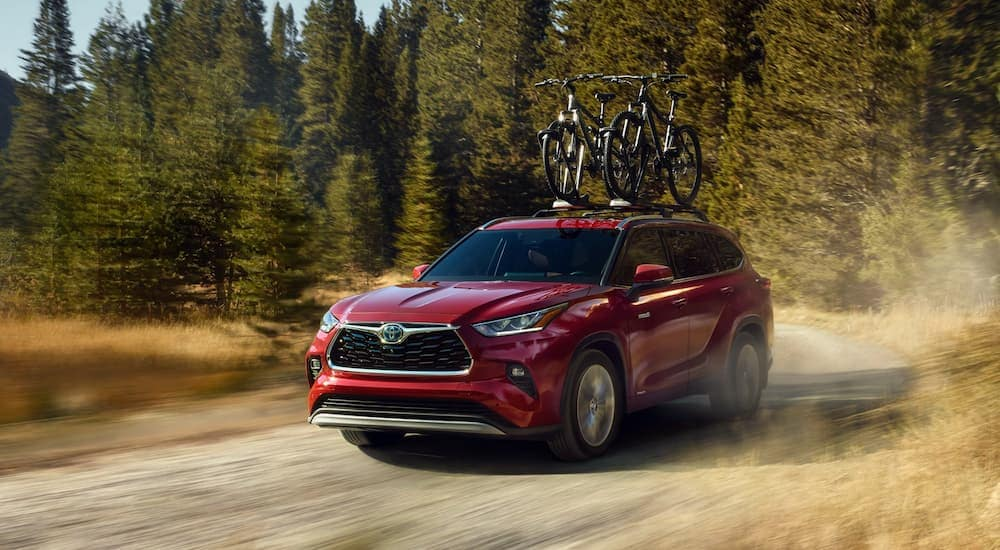 A red 2020 Toyota Highlander Hybrid is driving on a dirt road with bikes on the roof rack near Indiana, PA.