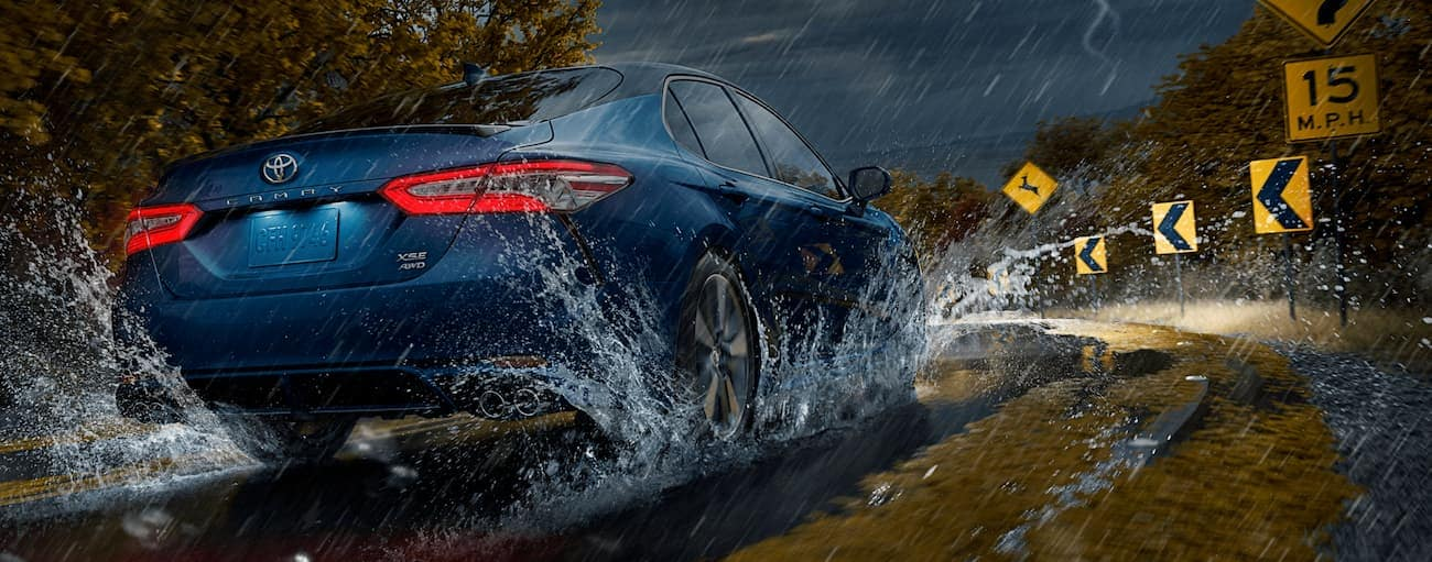 A blue 2020 Toyota Camry is driving in the rain towards a corner in Indiana, PA.