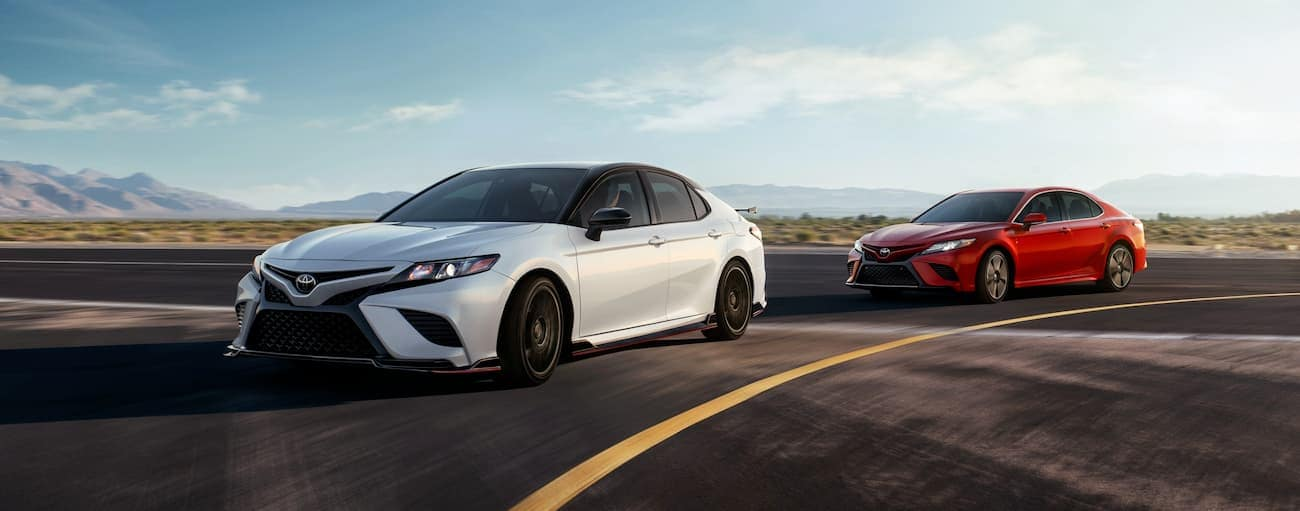 A red 2020 Toyota Camry is driving behind a white TRD Camry on a track.