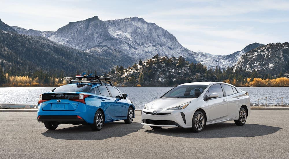 A blue and a white 2019 Toyota Prius are parked in front of a lake and mountains.