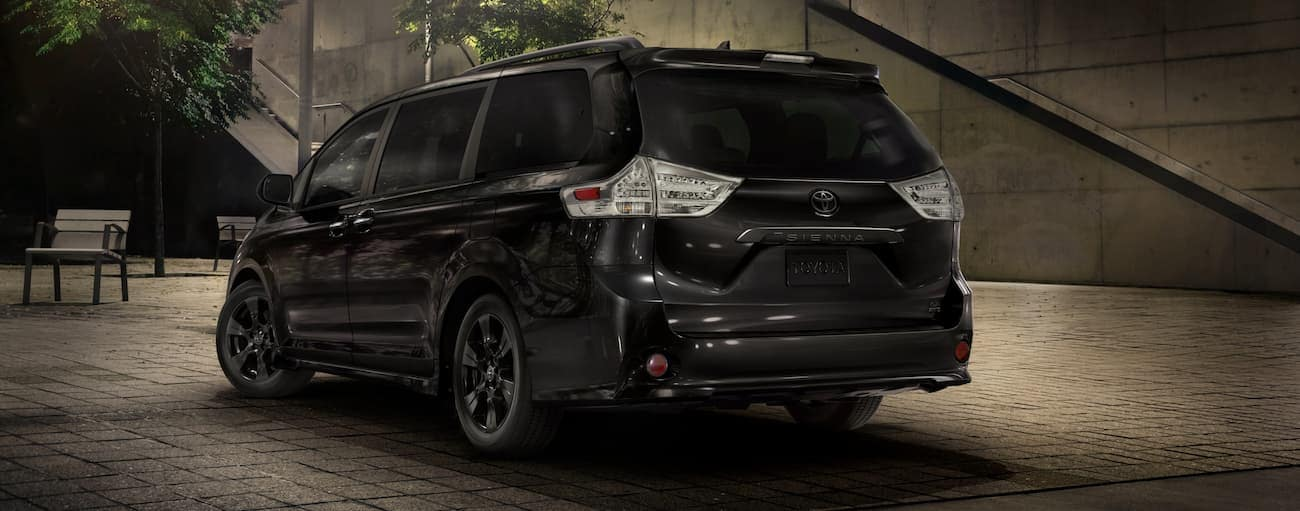 An all-black 2020 Toyota Sienna is parked on a city street at night.
