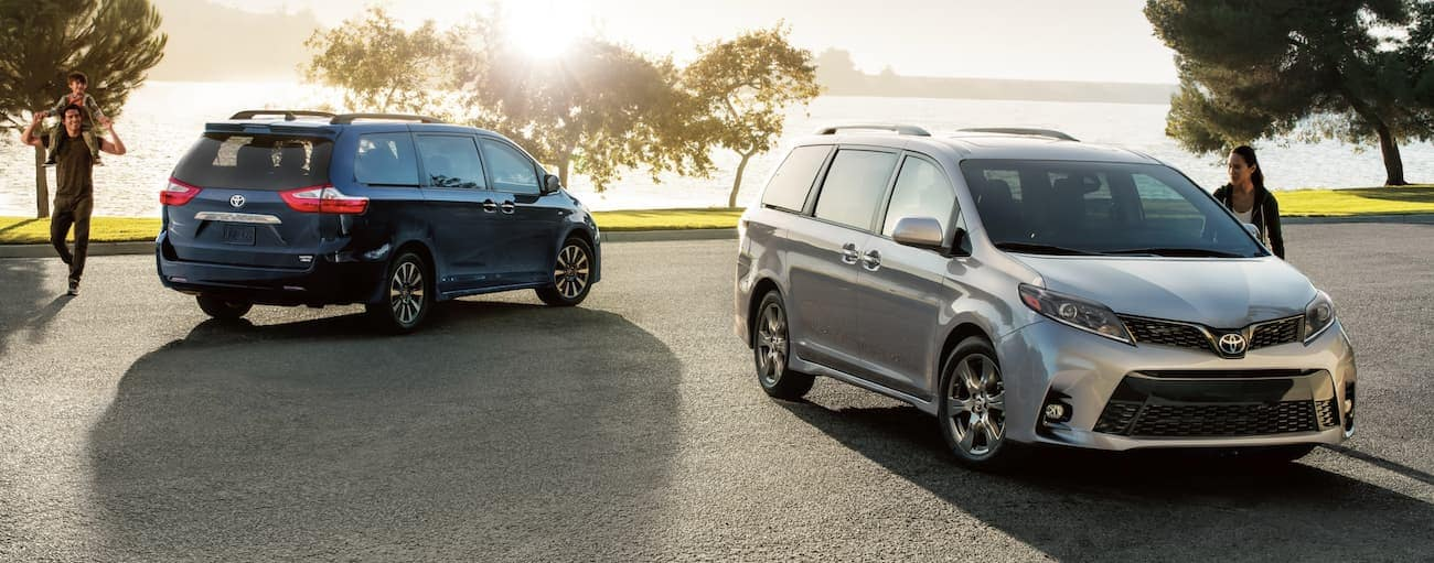 A silver SE Premium 2020 Toyota Sienna and a blue Limited Premium 2020 Toyota Sienna are parked in front of a body of water.