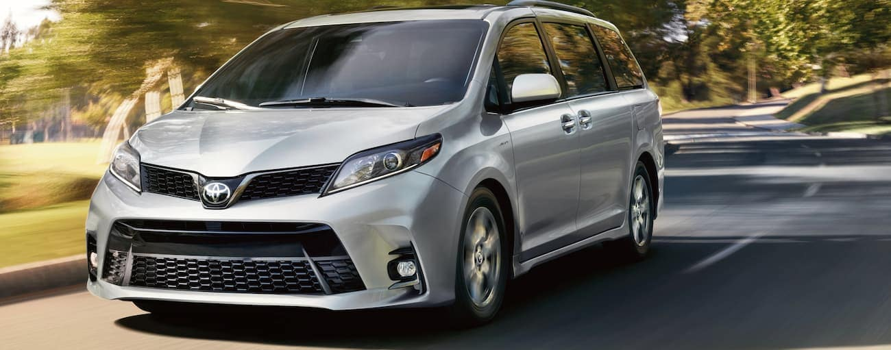 A silver 2020 Toyota Sienna is driving past sun shining through trees on a road near Indiana, PA.