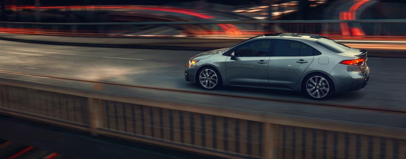 A grey-blue 2021 Toyota Corolla is driving on a city highway at night near Indiana, PA.