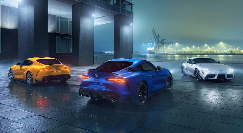 A yellow, a blue, and a silver 2021 GR Supra are parked in front of a city building at night.