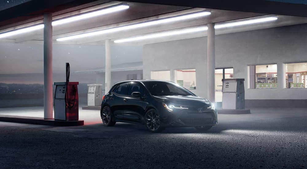 A black 2021 Toyota Corolla Hatchback is parked at a gas station at night.
