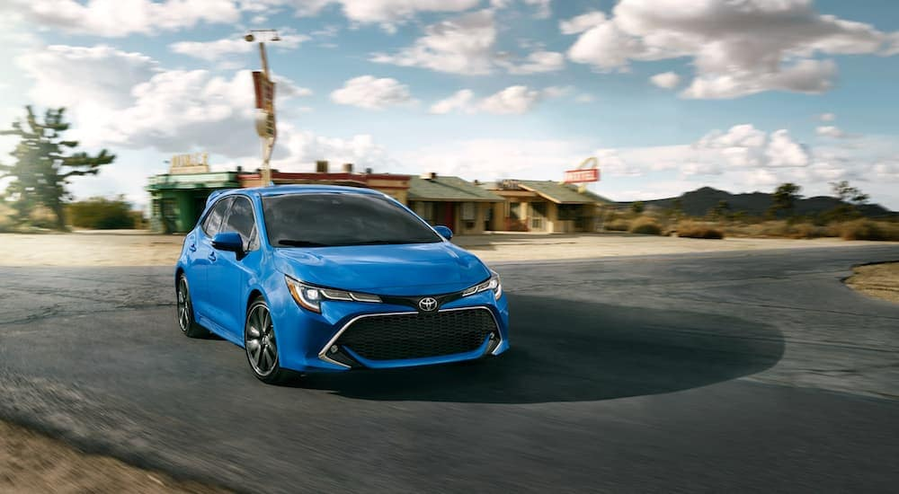 A blue 2021 Toyota Corolla Hatchback is driving through a rural intersection near Indiana, PA.