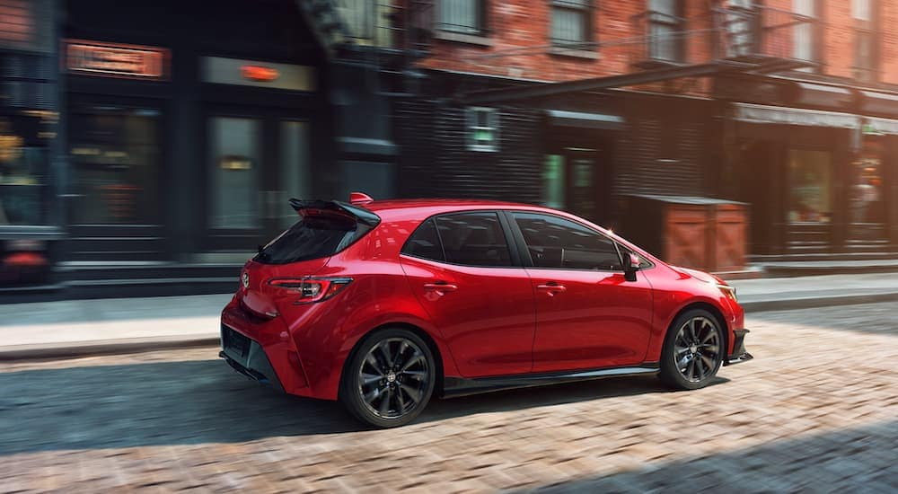 A red 2021 Toyota Corolla Hatchback is driving on a cobblestone street after leaving a Toyota dealership.