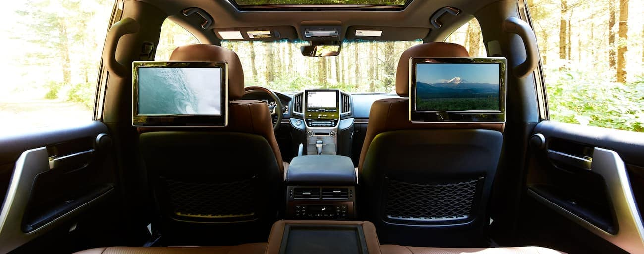 The tan interior with multiple screens is shown from the back seat forward in a 2021 Toyota Land Cruiser.