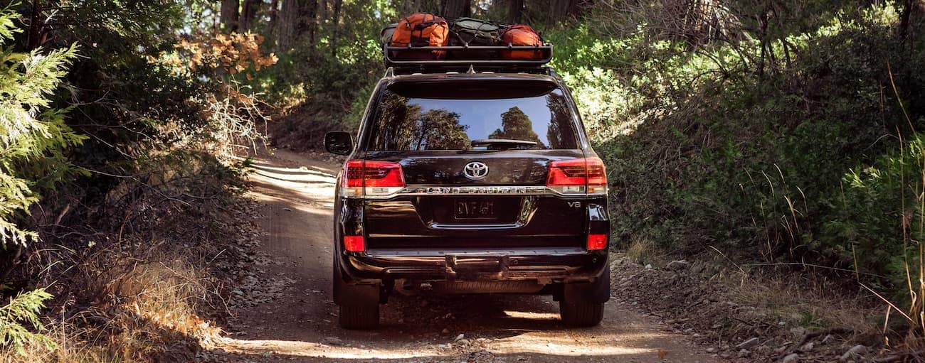 A black 2021 Toyota Land Cruiser is shown from the rear on a dirt trail with camping gear on the roof.