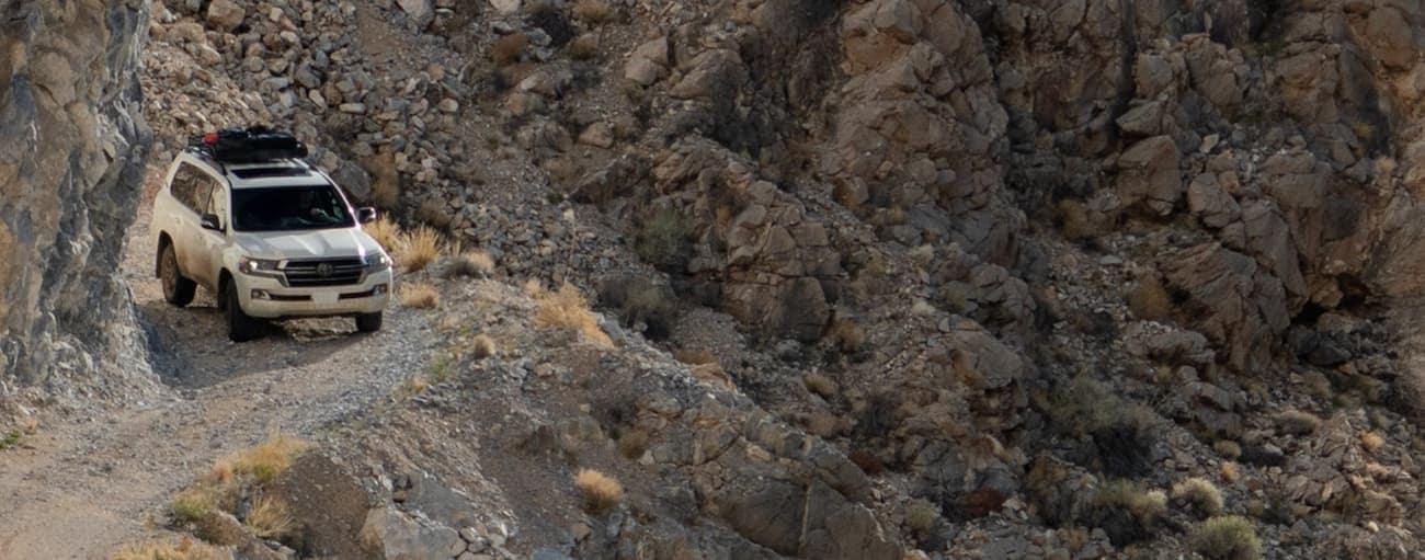 A white 2021 Toyota Land Cruiser is going around a corner on a narrow, rocky ledge.