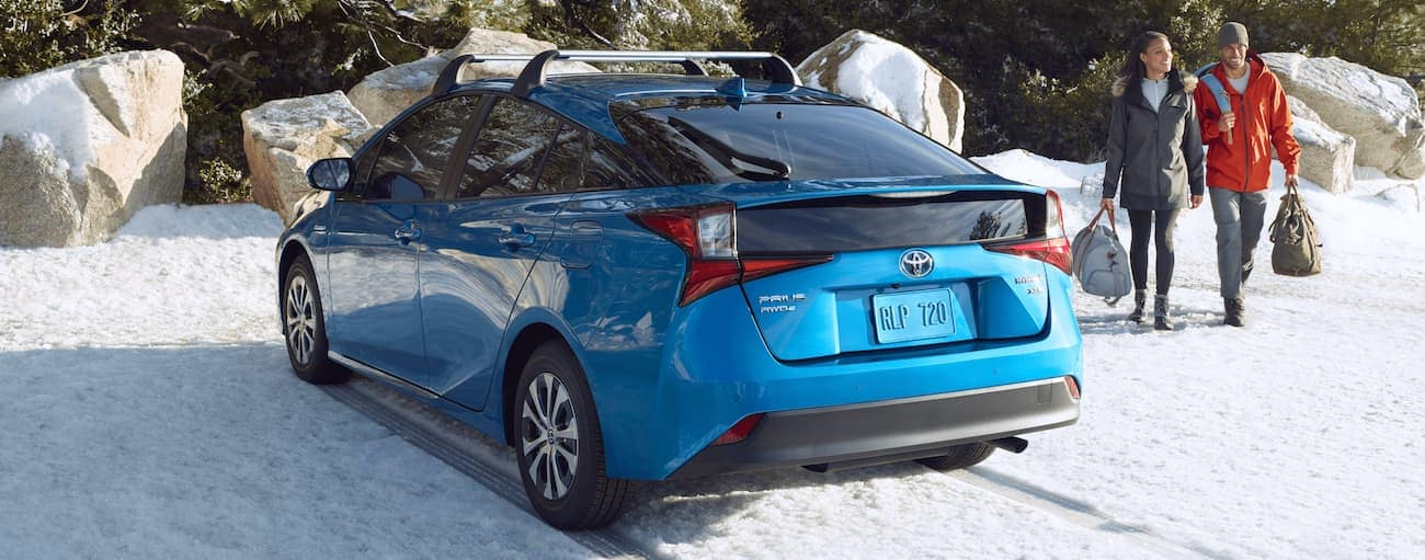 A couple is walking toward a blue 2021 Toyota Prius parked in the snow.