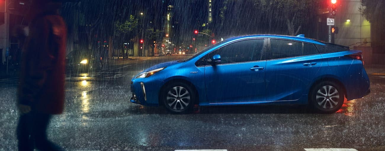 A blue 2021 Toyota Prius is driving on a city street at night in the rain.