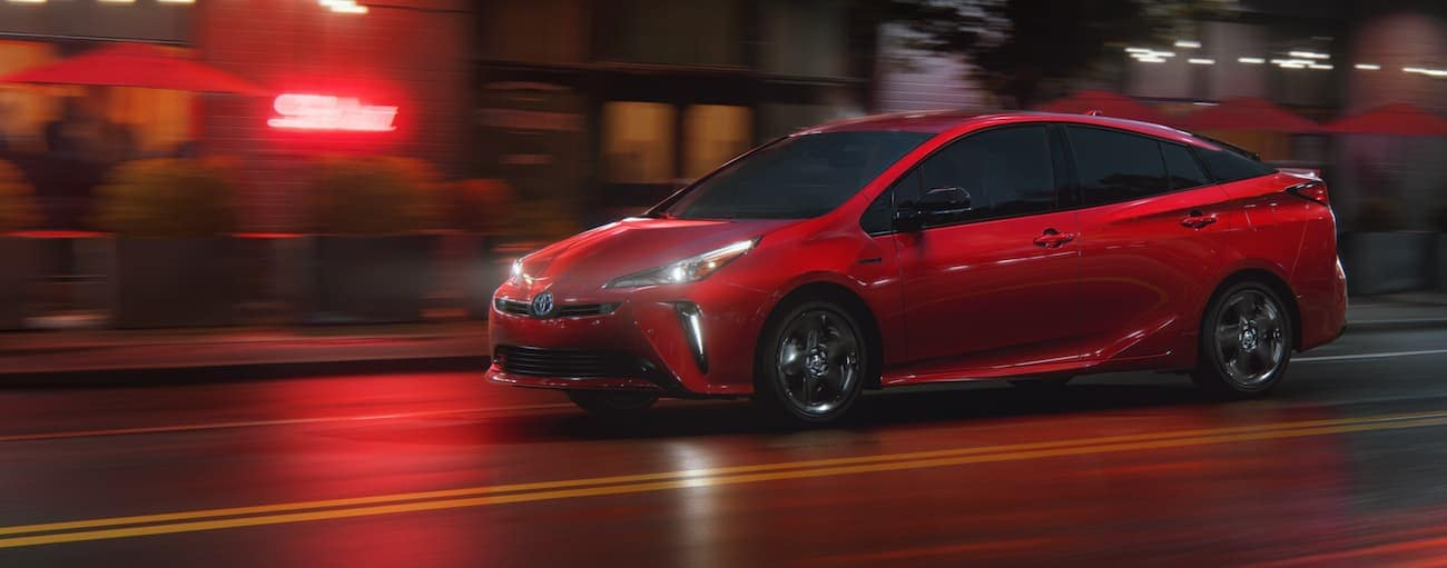 A red 2021 Toyota Prius is driving on a city street at night near Indiana, PA.