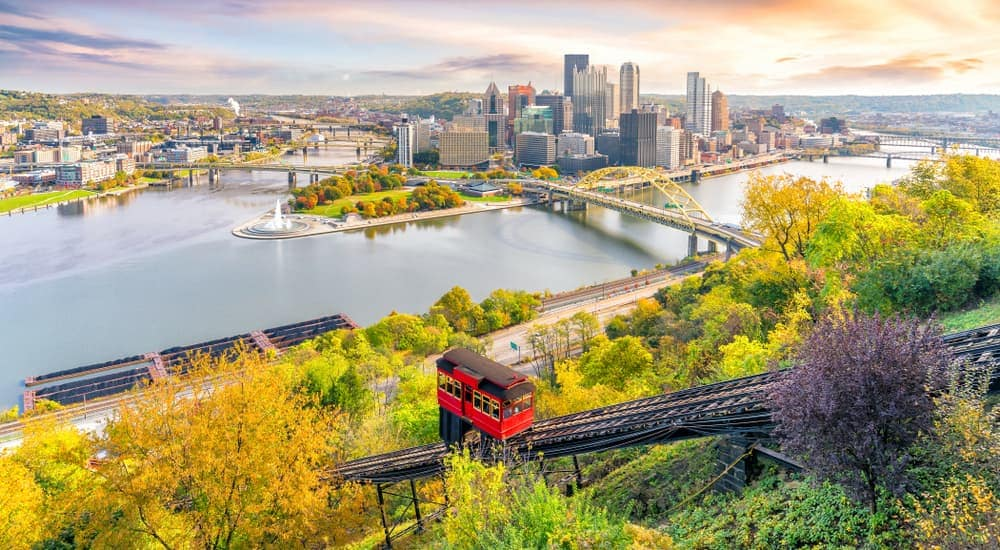 The Pittsburg, PA, skyline is shown from a hill with a trolley car going up a track.
