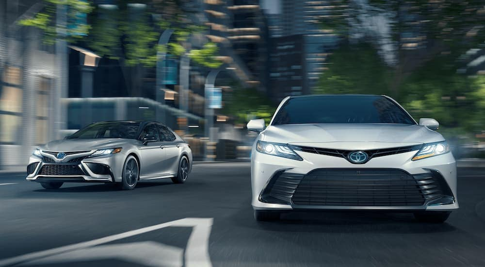 A silver and a white 2021 Toyota Camry are driving on a city street at night.