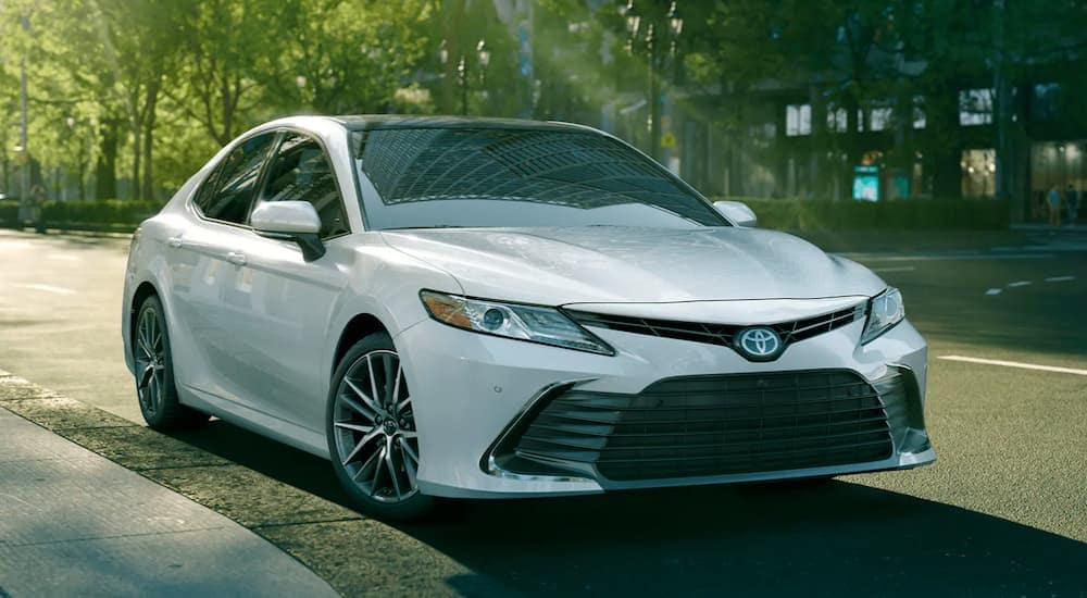 A white 2021 Toyota Camry is parked on a city street with trees after leaving a Toyota dealership near me.
