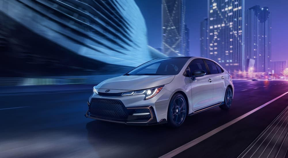 A white 2021 Toyota Corolla is driving through a city at night.