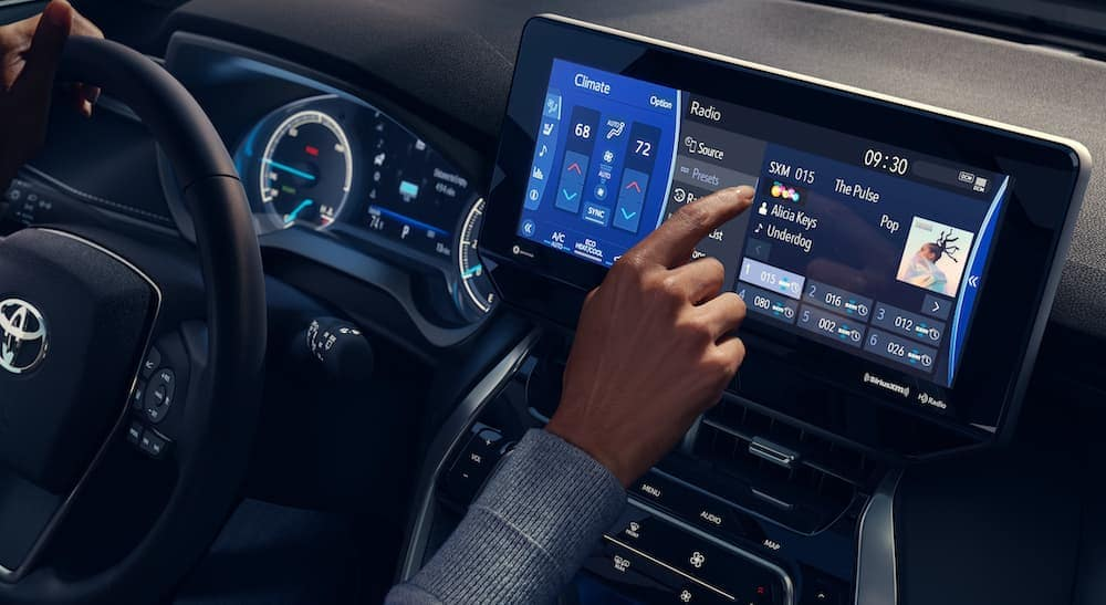 A closeup shows a person using the touch screen in a 2021 Toyota Venza, which is coming to a Toyota dealership near me.