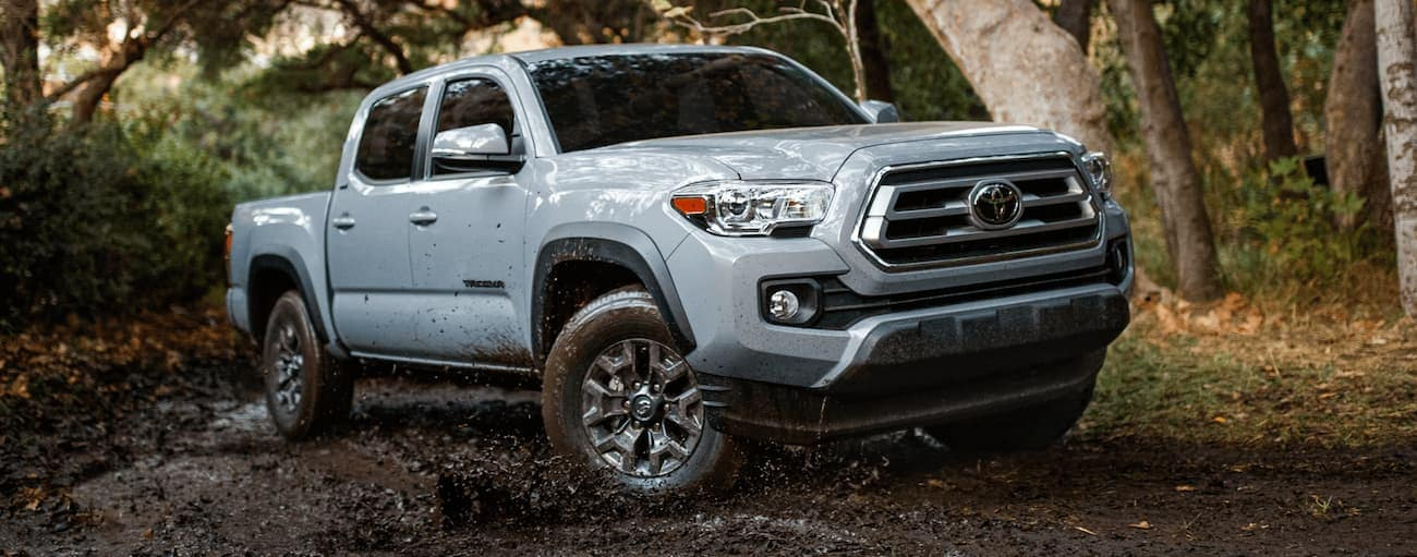 A light blue 2021 Toyota Tacoma is off-road in the woods.