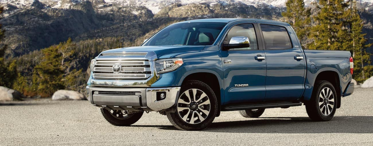 A blue 2021 Toyota Tundra is parked in front of snow capped mountains.