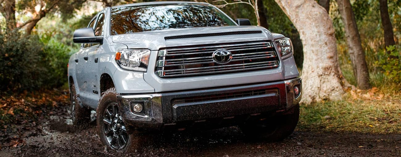 A silver 2021 Toyota Tundra is off-roading in the mud.
