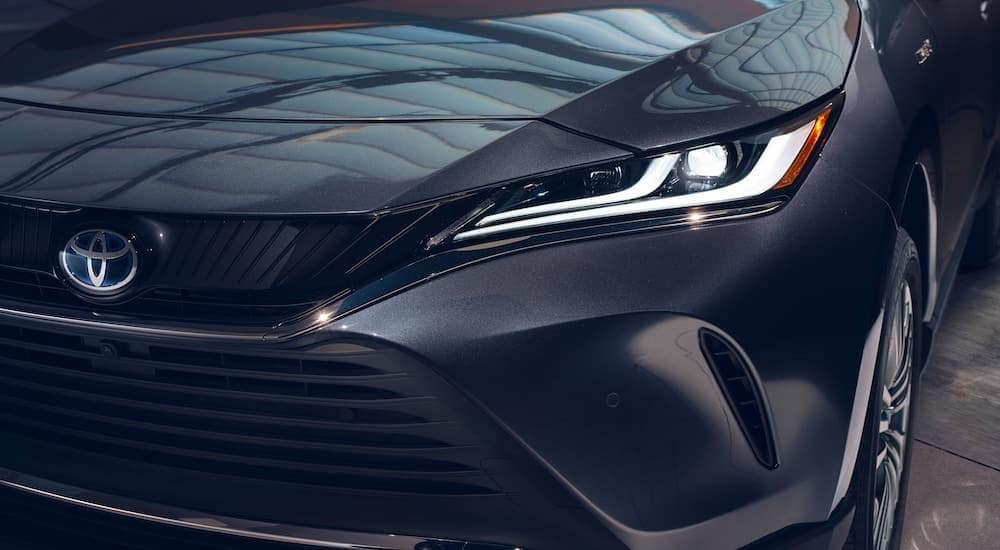 A close up of the driver side headlight is shown on a dark grey 2021 Toyota Venza.