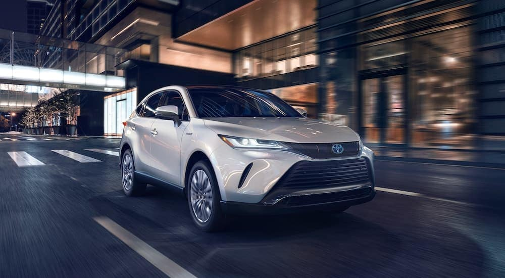 A silver 2021 Toyota Venza is driving down a city street after leaving Toyota Dealership.