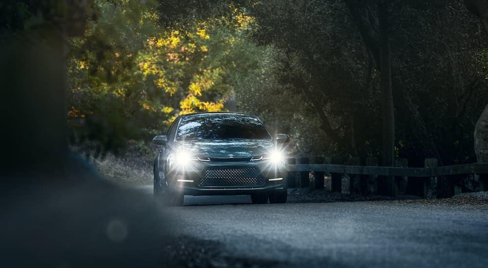 A popular Toyota Model, a blue 2021 Toyota Corolla XSE is driving down the road with its headlights on.