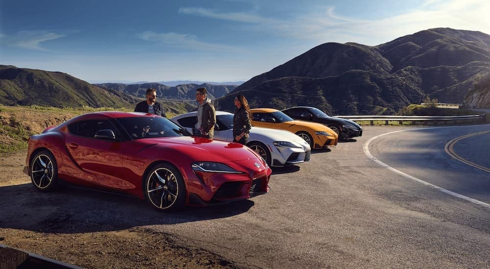 Four 2021 Toyota GR Supras are parked in a line on the side of the road, a red, a white, a yellow, and a black.