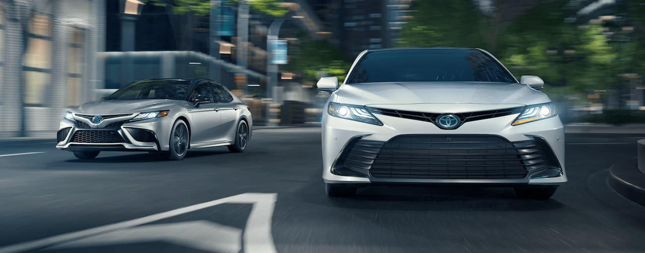 A white and a silver 2021 Toyota Corolla Hybrid are driving on a city street at night.