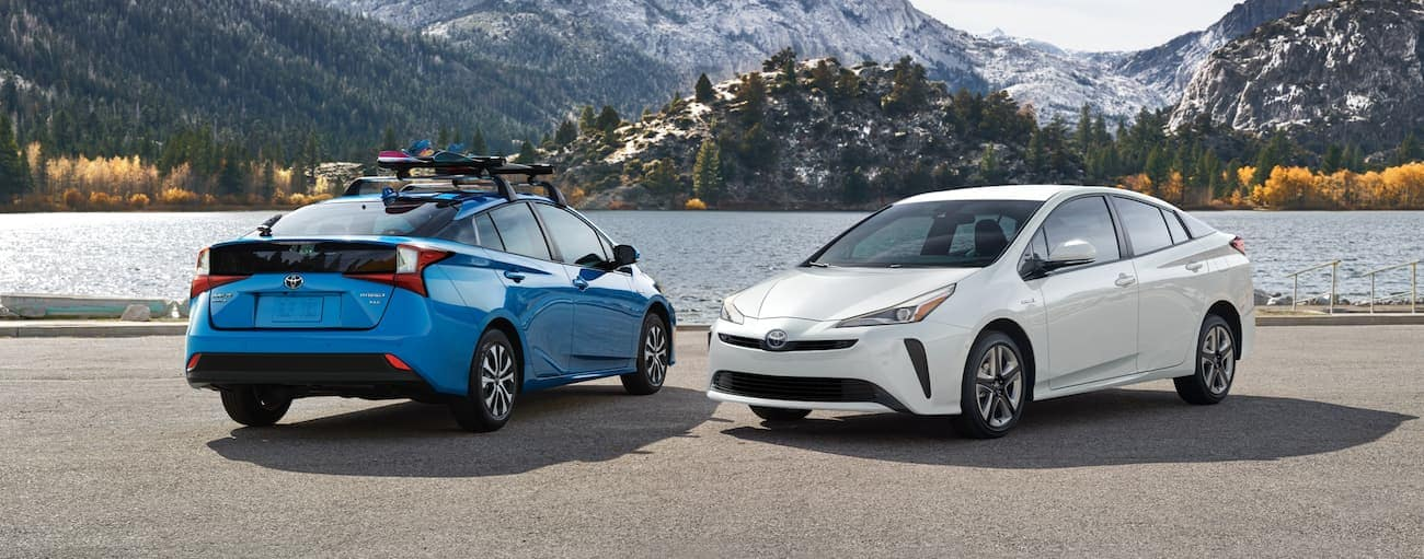 Two 2021 Toyota hybrids, a blue and a white Prius, are parked in front of a lake.