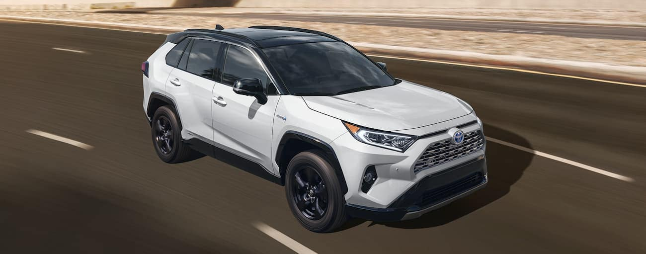 A white 2021 Toyota RAV4 Hybrid is driving on a highway.