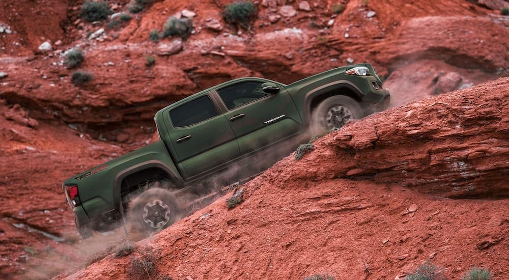 A green 2021 Toyota Tacoma TRD is shown in profile driving up a steep desert incline.