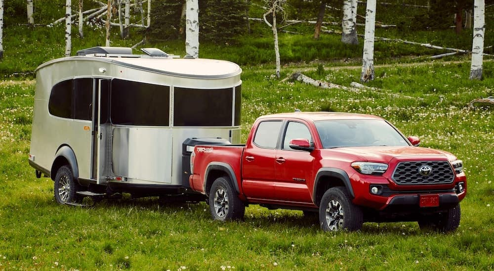 A red 2021 Toyota Tacoma TRD is parked in the grass and angled right while attached to a trailer.
