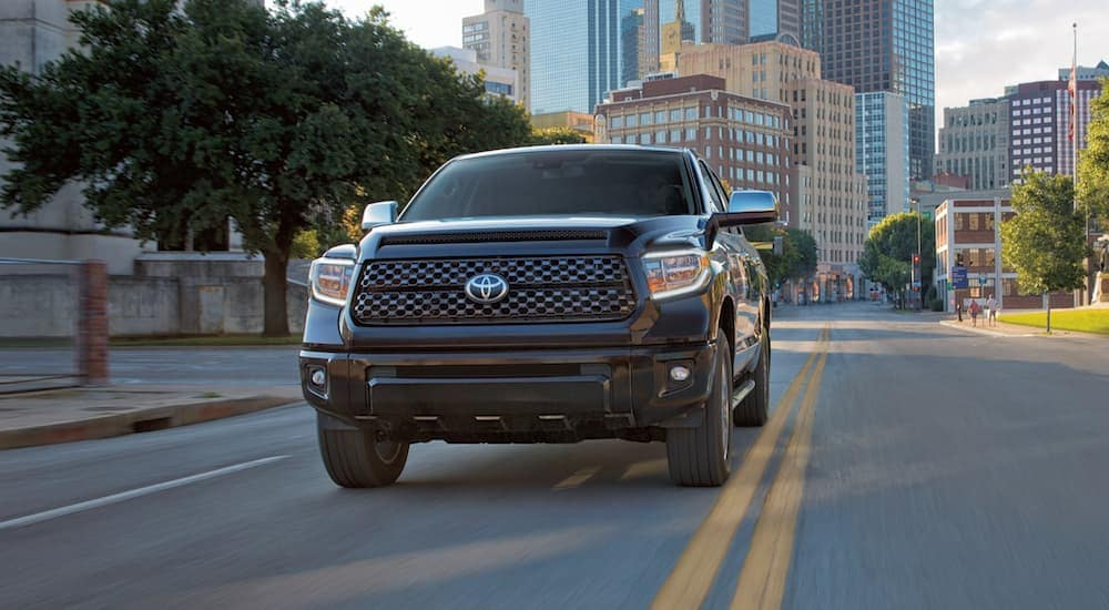 A black 2021 Toyota Tundra is shown from the front driving on a city street.