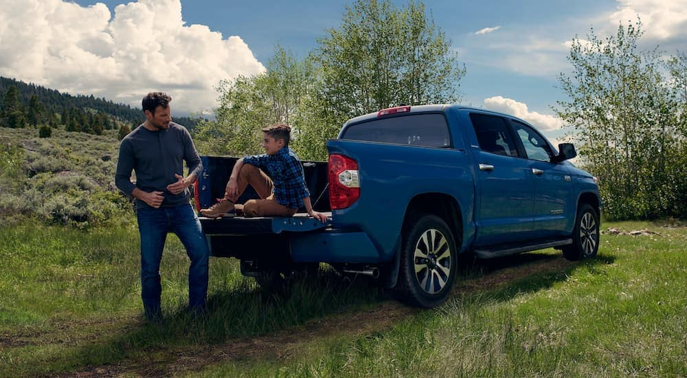 A man is talking to his son who is sitting on the tailgate of a blue 2021 Toyota Tundra that is parked on grass.