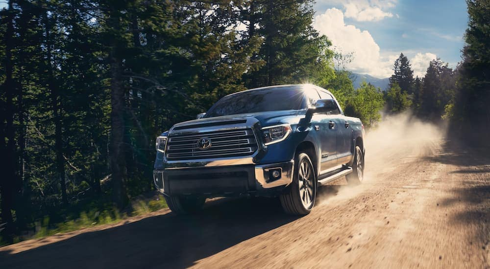 A blue 2021 Toyota Tundra is driving on a dirt road.