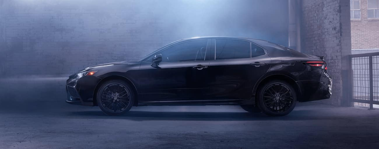 A black 2021 Toyota Camry Nightshade edition is in a dimly lit garage.