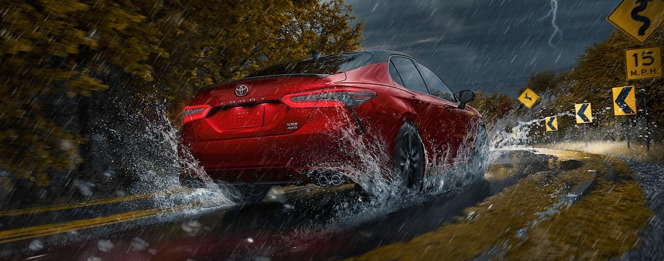 A red 2021 Toyota Camry is driving toward a sharp corner with warning signs in the rain.