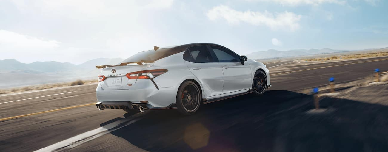 A white 2021 Toyota Camry is pulling off on a desert highway exit after winning the 2021 Toyota Camry vs 2021 Honda Accord comparison.