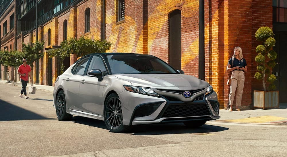 A silver 2021 Toyota Camry Hybrid is parked in front of a brick building on a city street after leaving a Toyota hybrid dealer.